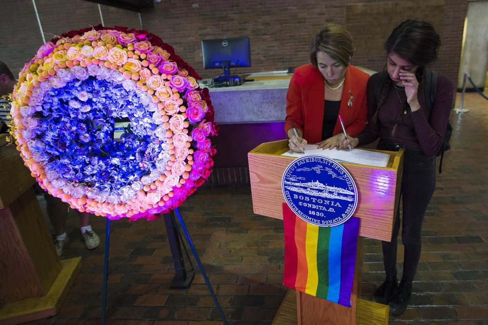 Attorney General Maura Healey signed the condolence book with Maya Saxen of Orlando who said she knew a few of the victims at the Pulse Dance Club. The condolence book will continue to be available at City Hall. (Jesse Costa/WBUR)