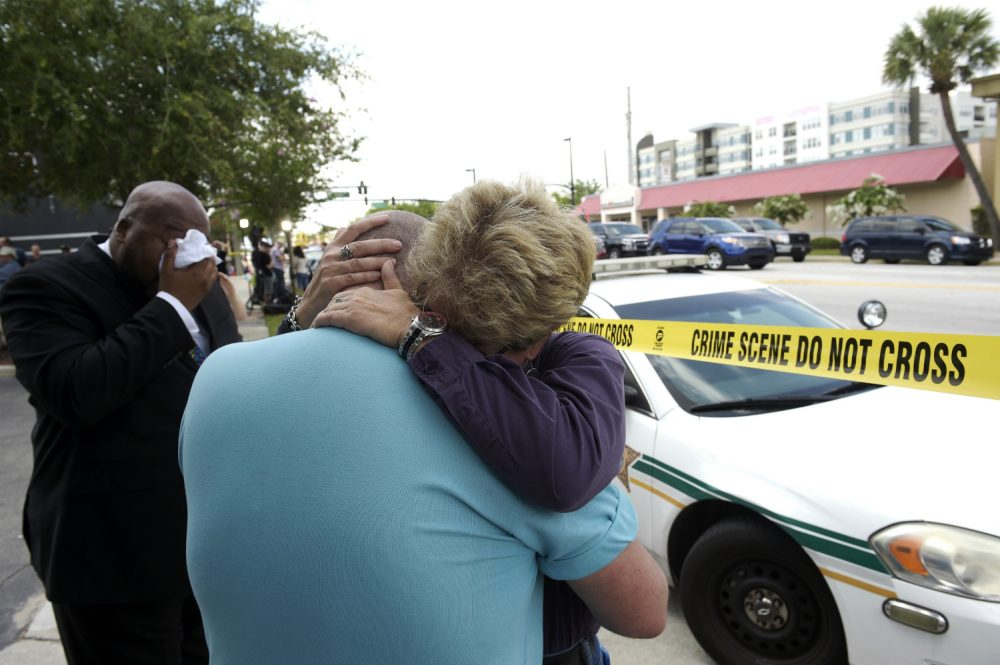 Terry DeCarlo, executive director of the LGBT Center of Central Florida, center, is comforted by Orlando City Commissioner Patty Sheehan, right, after a shooting involving multiple fatalities at a nightclub in Orlando, Fla., Sunday, June 12, 2016. (Phelan M. Ebenhack/AP)
