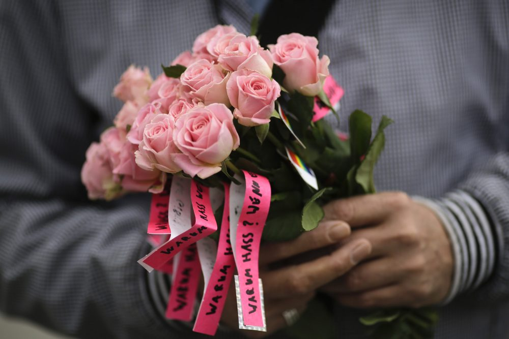 A man holds a bunch of flowers with small ribbons reading 'Why Hatred? If there is love.' during a vigil in front of the United States embassy in Berlin, German, on Monday to honor the victims. (Markus Schreiber/AP)