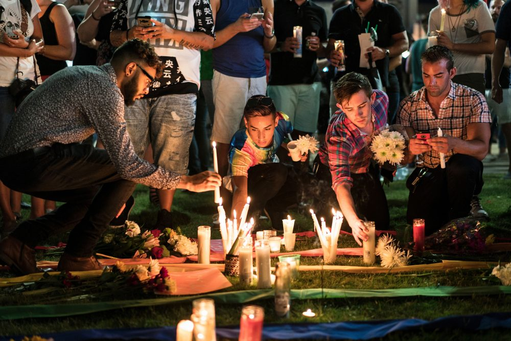 People make a memorial after a vigil outside the Dr. Phillips Center for the Performing Arts for the mass shooting victims at the Pulse nightclub June 13, 2016 in Orlando, Florida. The American gunman who launched a murderous assault on a gay nightclub in Orlando was radicalized by Islamist propaganda, officials said Monday, as they grappled with the worst terror attack on US soil since 9/11.  (BRENDAN SMIALOWSKI/AFP/Getty Images)