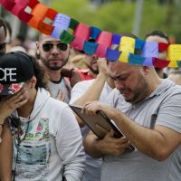 Jose Hernandez, right, cries as he looks at a photo of his friend Amanda Alvear, who was killed in the mass shooting at the Pulse nightclub, as he visits a makeshift memorial with friends, Monday, June 13, 2016, in Orlando, Fla. (David Goldman/AP)