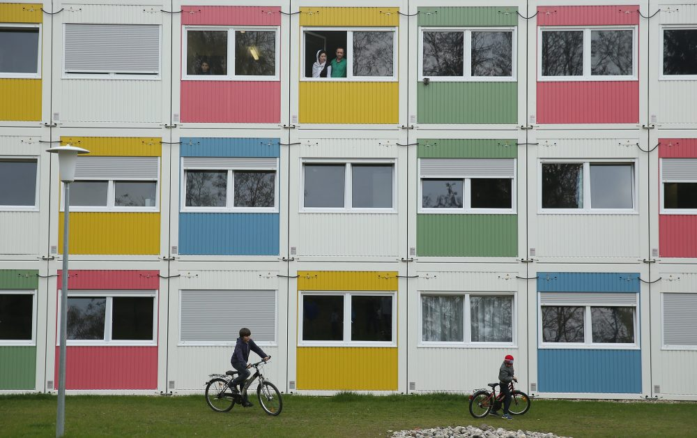 Children play as residents look from their window at the container settlement shelter for refugees and migrants in Zehlendorf district on April 14, 2016 in Berlin, Germany. (Sean Gallup/Getty Images)