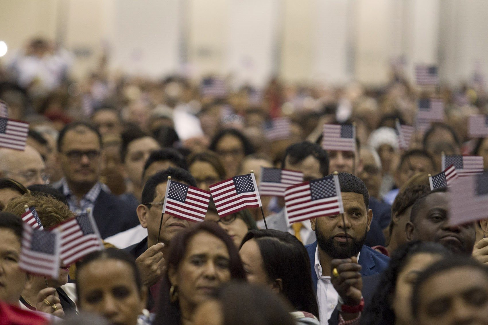 "New U.S. citizens wave flags during a rendition of ""America the Beautiful"" at the Hynes Convention Center Thursday. (Joe Difazio for WBUR)"