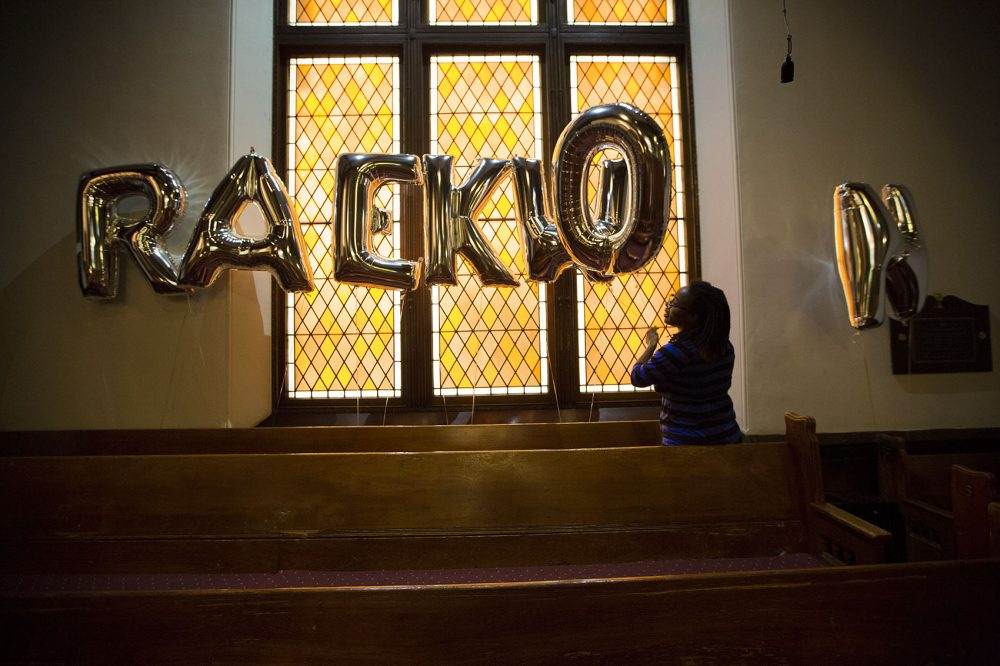Raekwon Brown's cousin, sets up balloons spelling out his name before his funeral ceremony Thursday. (Jesse Costa/WBUR)