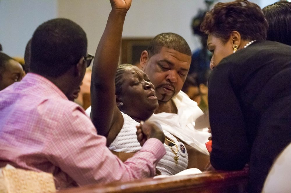 A grieving Wanda Graddy, Raekwon Brown's mother, is comforted by friends and family. (Jesse Costa/WBUR)