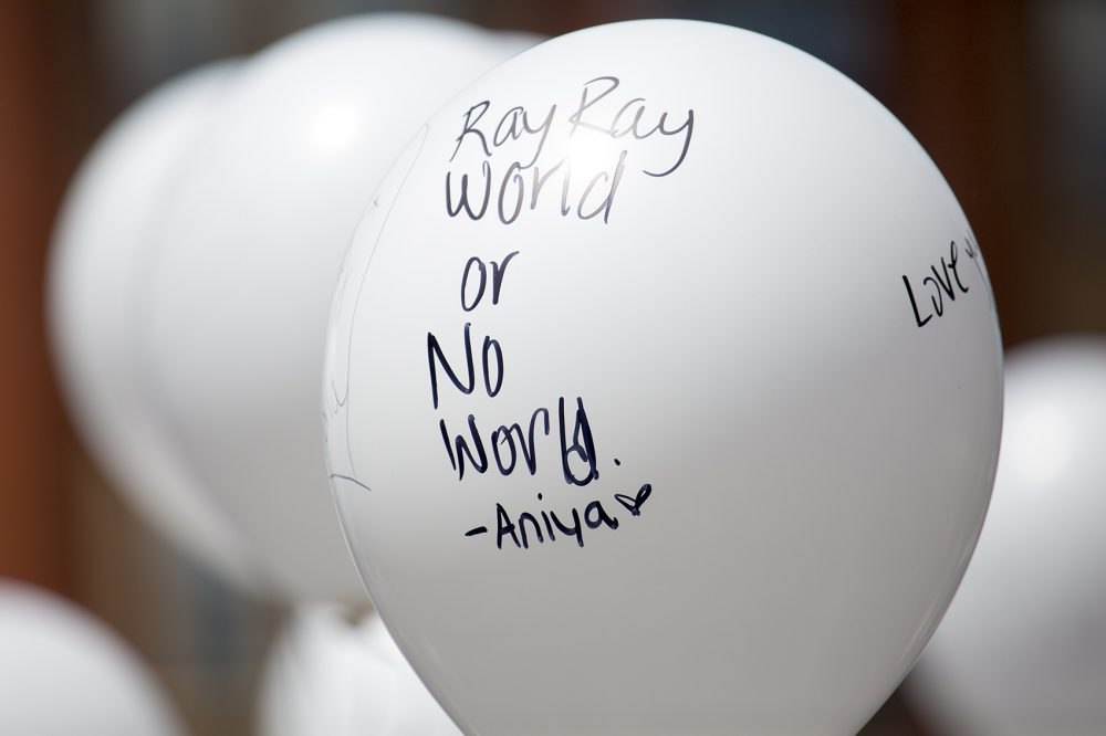 Mourners wrote personal messages on white balloons, which were given out to Burke High School students to release into the air at the burial site. (Jesse Costa/ WBUR)
