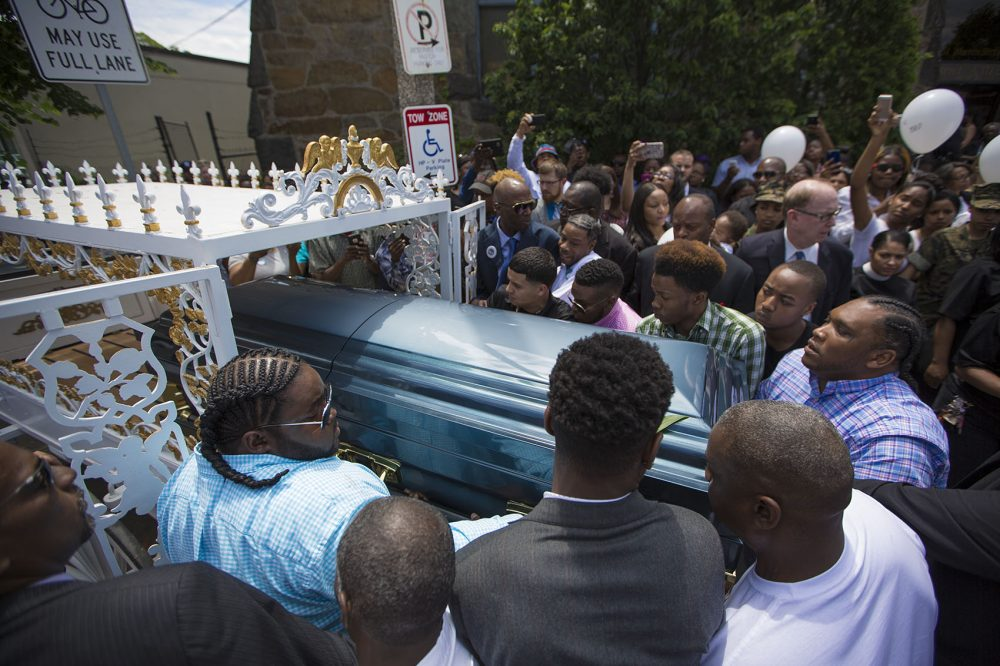 Pallbearers put Raekwon's casket into a horse-drawn carriage that took him to the burial site. (Jesse Costa/WBUR)