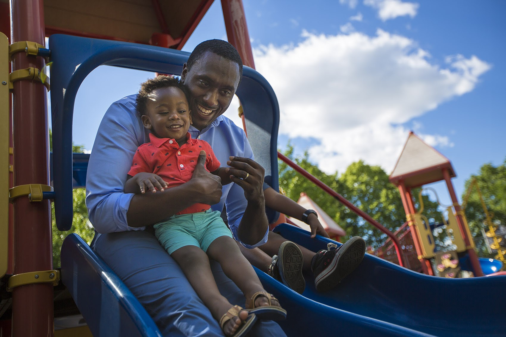 Charles Daniels, founder and CEO of the Boston-based nonprofit Fathers' Uplift, rides down a slide with his 1-year-old son Clayton in the Thetford Evans Playground in Dorchester. (Jesse Costa/WBUR)