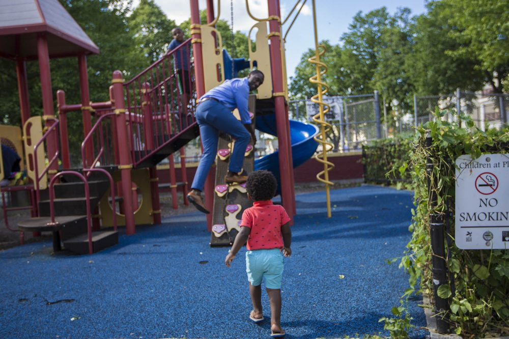 Charles Daniels plays with his one-year-old son Clayton in the Thetford Evans Playground in Dorchester. (Jesse Costa/WBUR)