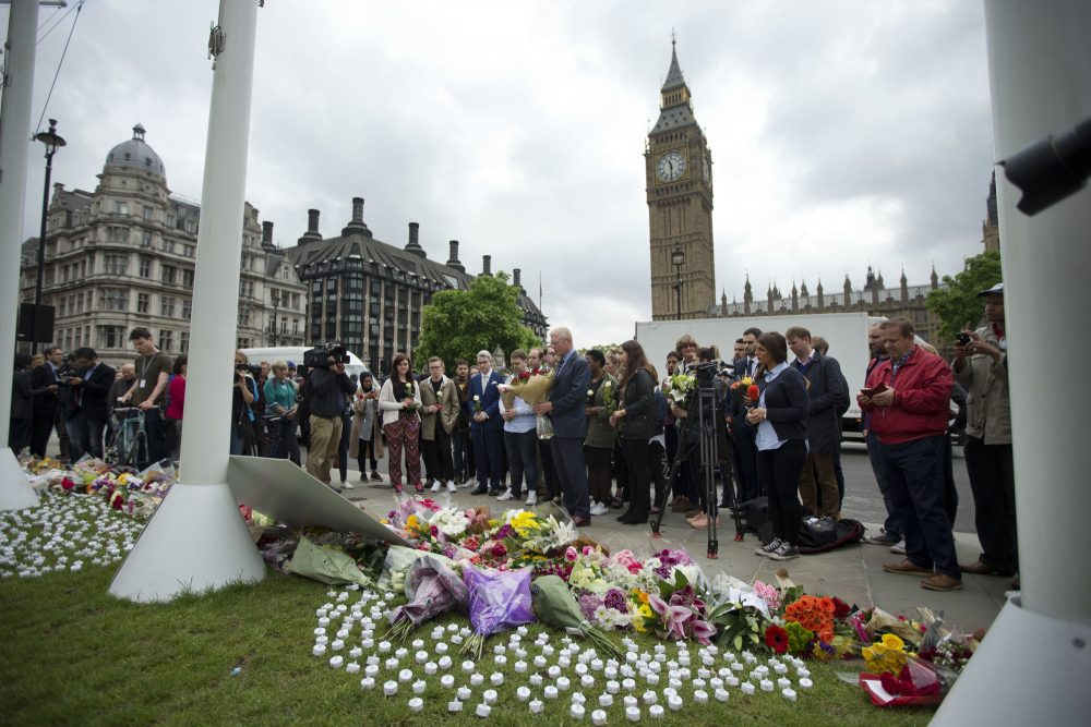 Staff from Britain's opposition Labour Party stand together before placing floral tributes for their colleague Jo Cox, the 41-year-old British Member of Parliament shot to death yesterday in northern England, on Parliament Square outside the House of Parliament in London, Friday, June 17, 2016. (AP Photo/Matt Dunham)
