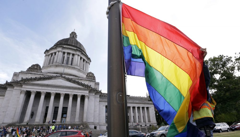 A state worker unfurls a rainbow flag in front of the Washington state Capitol to prepare it to be raised and then lowered to half-staff to mark last weekend's mass shooting at a central Florida nightclub.Wednesday, June 15, 2016, in Olympia, Wash. A gunman wielding an assault-type rifle and a handgun opened fire inside Pulse, a crowded gay nightclub in Orlando, Florida, early Sunday, leaving at least 49 people dead in the worst mass shooting in modern U.S. history. (AP Photo/Elaine Thompson)