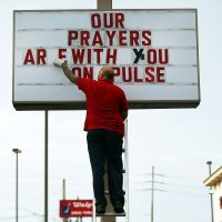 Jiffy Lube employee Ralph Nieves put up a sign of support for the Orlando community following the shooting at the Pulse nightclub last Saturday night on June 16, 2016 in Orlando, Florida. (Spencer Platt/Getty Images)