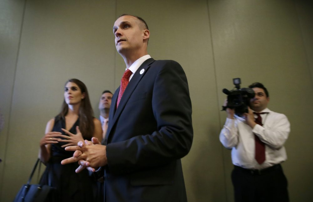 In this photo taken Aug. 25, 2015, Republican presidential candidate Donald Trump's campaign manager Corey Lewandowski watches as Trump speaks in Dubuque, Iowa. Florida police have charged Lewandowski with simple battery in connection with an incident earlier in the month involving a reporter. (Charlie Neibergall/AP)