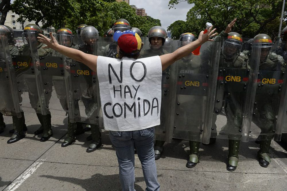 """A woman with a sign reading """"There is no food"""" protests against new emergency powers decreed this week by President Nicolas Maduro in front of a line of policemen in Caracas on May 18, 2016. (Federico Parra /AFP/Getty Images)"""