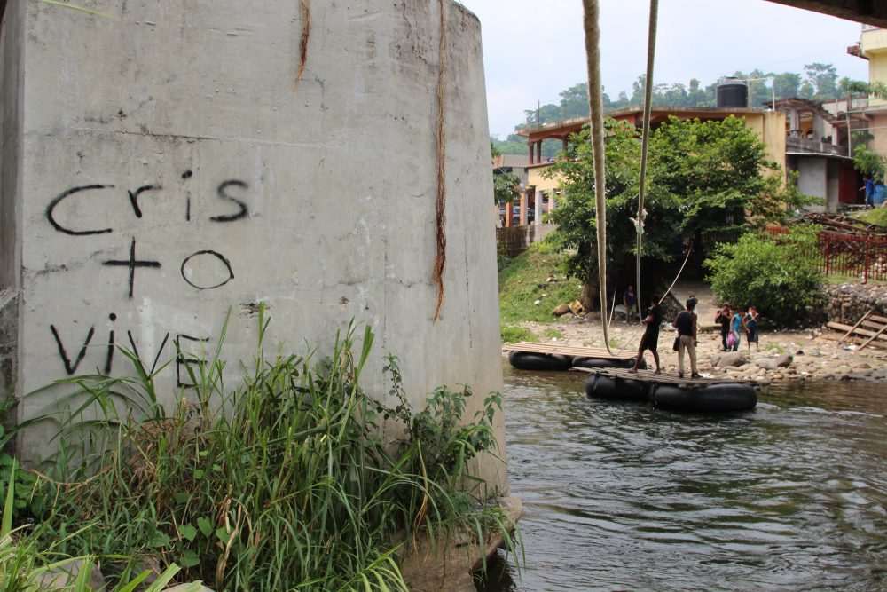 """The words read, """"Christ Lives."""" Migrants and goods such as oil and foodstuffs are transported illegally on a raft below this bridge, an official port of entry linking Mexico and Guatemala. (Lorne Matalon/Fronteras)"""