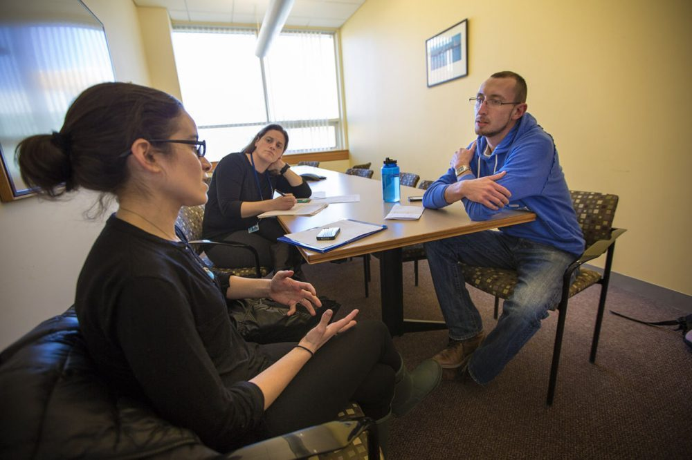 Justin Marotta, right, takes his oral mid-term exam for a suicide prevention course at the Simmons College School of Social Work. Laura Goodman, left, is role-playing as the client, as course instructor Kim O'Brien observes. (Jesse Costa/WBUR)