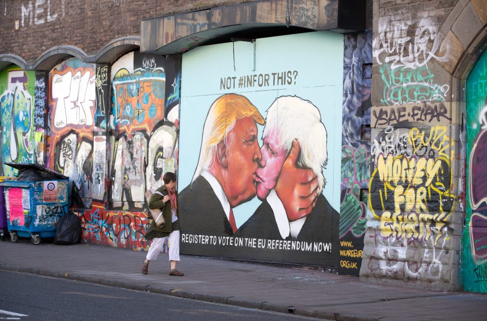 A woman passes a mural that has been painted on a derelict building in Stokes Croft showing US presidential hopeful Donald Trump sharing a kiss with former London Mayor Boris Johnson on May 24, 2016 in Bristol, England. Boris Johnson is currently one of the biggest names leading the campaign for Britain to leave the European Union in the referendum which takes place on June 23 and Republican presidential hopeful Donald Trump has also backed a so-called Brexit.  (Matt Cardy/Getty Images)