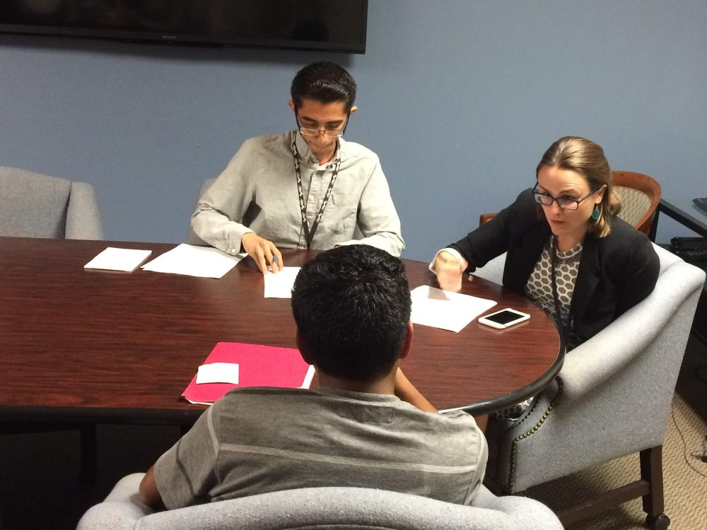 Legal assistant Javier Hernandez and lawyer Sara Van Hofwegen of Public Counsel meet with a teenage client from Guatemala who is applying for asylum. (Jude Joffe-Block/Fronteras)