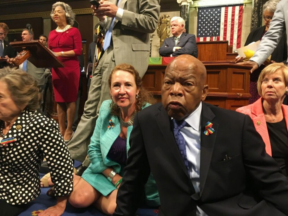 This photo provided by Rep. Chillie Pingree, D-Maine, shows Democrat members of Congress, including Rep. John Lewis, D-Ga., center, and Rep. Elizabeth Esty, D-Conn. as they participate in sit-down protest seeking a a vote on gun control measures, Wednesday, June 22, 2016, on the floor of the House on Capitol Hill in Washington.  (Rep. Chillie Pingree via AP)