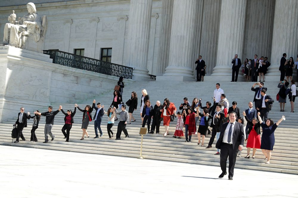 Immigration supporters hold up their hands and walk down the steps of the U.S. Supreme Court April 18, 2016 in Washington, DC. The Supreme Court heard oral arguments in the case of United States v. Texas, which is challenging President Obama's 2014 executive actions on immigration - the Deferred Action for Children Arrivals (DACA) and Deferred Action for Parents of American and Lawful Permanent Residents (DAPA) programs.  (Alex Wong/Getty Images)