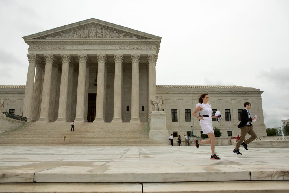 Interns race to deliver hard copies of a Supreme Court decision regarding Obama's immigration plan to waiting news crews at the U.S. Supreme Court, on June 23, 2016 in Washington, DC.  The court was divided 4-4, leaving in place an appeals court ruling blocking the plan, which would have protected millions of immigrants from deportation. (Allison Shelley/Getty Images)