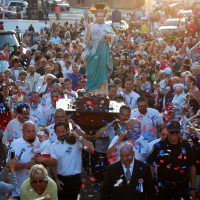 The statue of St. Peter is showered with confetti as it's carried into Gloucester's St. Peter's Square during the opening ceremonies of the St. Peter's Fiesta, June 24, 2016. (Greg Cook)