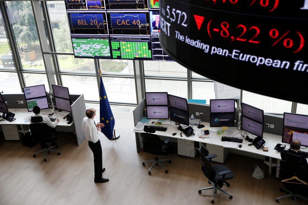 People work as screens display news and trading rates at the Euronext Stock Exchange services in Paris' financial district of La Defense on June 24, 2016 as Britain votes to leave the European Union, fuelling a wave of global uncertainty. (Thomas Samsom/AFP/Getty Images)