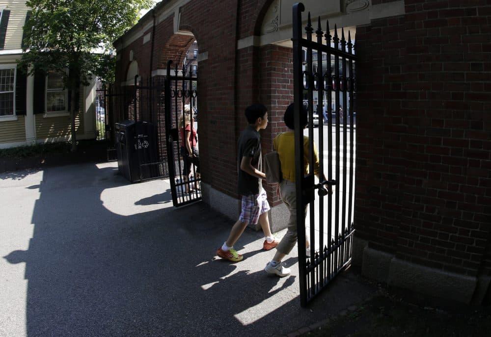 Pedestrians walk through a gate on Harvard University's campus. (Elise Amendola/AP)