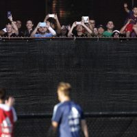 Argentina's Lionel Messi, left, waves to fans after a practice Thursday at Harvard University. (Charles Krupa/AP)