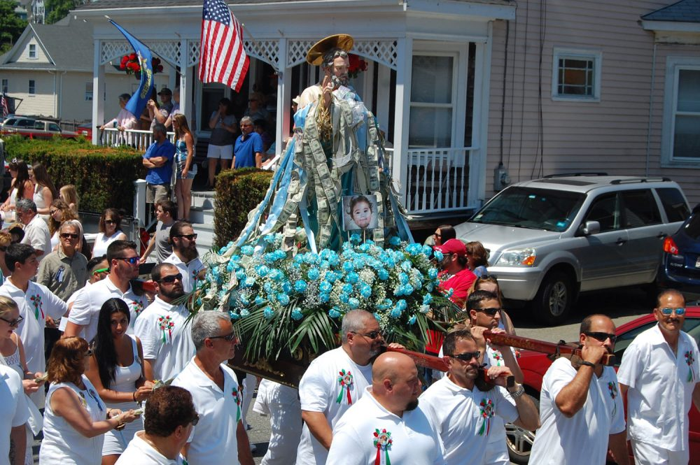 The St. Peter statue is carried up Prospect Street in Gloucester during the St. Peter's Fiesta in 2016. (Greg Cook/WBUR)