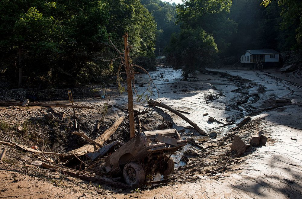 A truck lies in a hole among the mud after it was washed out of the driveway from the flooding on June 25, 2016 in Clendenin, West Virginia. The flooding of the Elk River claimed the lives of 26 people in West Virginia. (Ty Wright/Getty Images)