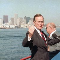 "Vice President George H.W. Bush gestures while touring the Boston Harbor by boat, Sept. 1, 1988, during a brief campaign stop in Boston. Bush's campaign, which labeled Boston Harbor as ""the dirtiest harbor in America"" served as a catalyst for the clean up of the waters. (Peter Southwick/AP)"