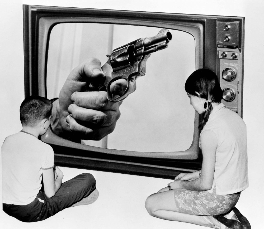 "Steve Almond: There is a more direct means of making your voice heard on gun violence in this country: Divest from the gun industry. Pictured: A composite of two children looking at a hand holding a gun on a TV screen, in New York, June 21, 1968. The original caption asked: ""Will we ever see the day when the fist clenched around the grip of a deadly weapon will cease being shown as 'part of the times' we live in?"" Almost 48 years to the day later, America has yet to solve its problem of gun violence. (Bob Wands/AP)"
