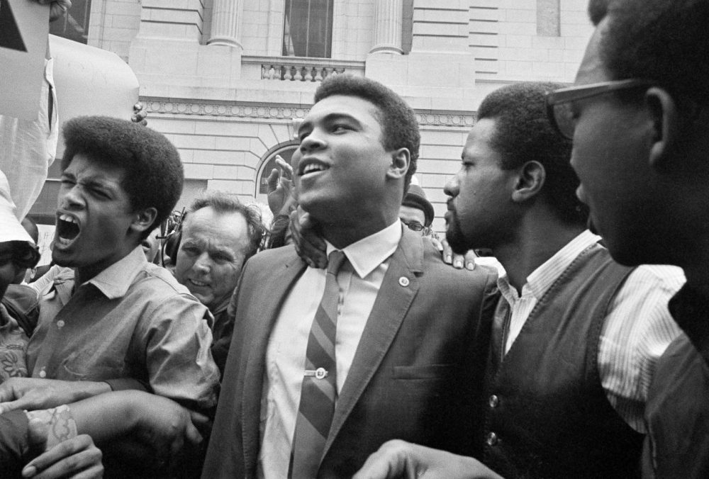 Muhammad Ali, center, leaves the Armed Forces induction center with his entourage after refusing to be drafted into the Armed Forces in 1967.  (AP Photo)
