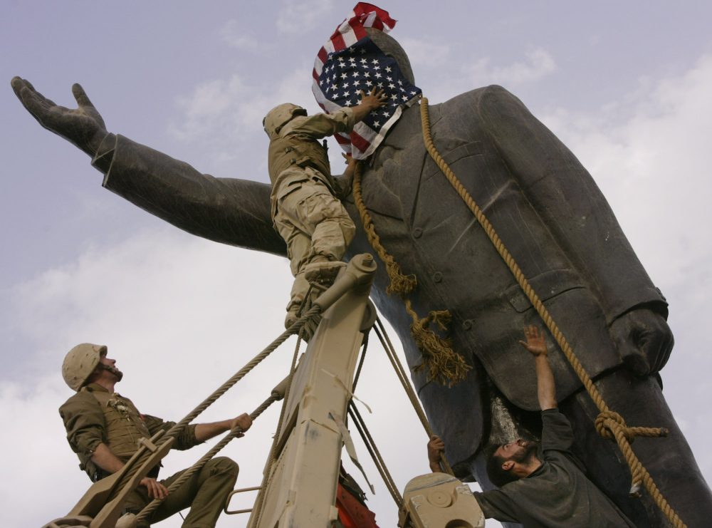 Neta C. Crawford does the math and asks: Has the War on Terror been money well spent?  Pictured: Wednesday, April 9, 2003, an Iraqi man, bottom right, watches Cpl. Edward Chin of the 3rd Battalion, 4th Marines Regiment, cover the face of a statue of Saddam Hussein with an American flag before toppling the statue in downtown in Baghdad, Iraq. Thirten years after the U.S. invaded Iraq to topple Saddam Hussein, the country is still mired in war. (Jerome Delay/AP File)