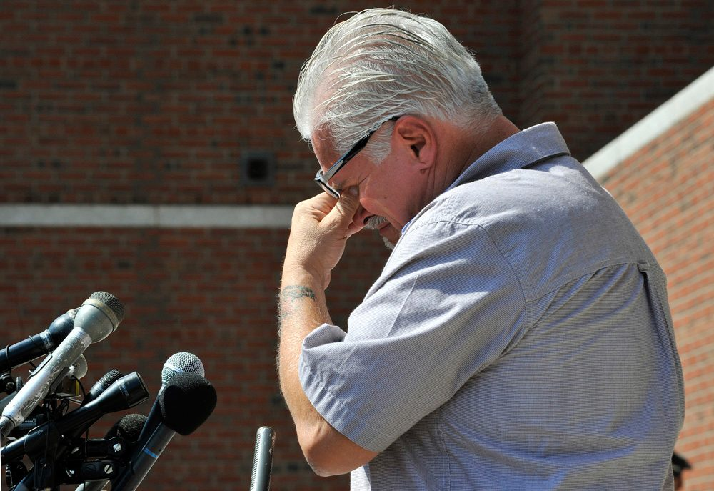 Stephen Davis, brother of murder victim Debra Davis, cries outside of Boston federal court while speaking with reporters. (WBUR)