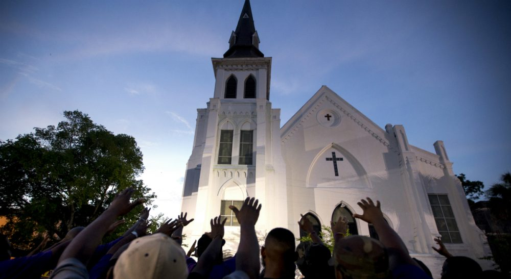 """Mark Edington: """"We don't need more weapons to make ourselves safer. We need more places of pilgrimage. And we need to go, not as tourists, but as pilgrims — people willing to be changed."""" Pictured: A crowd of people in prayer outside the Emanuel AME Church, Friday, June 19, 2015. Nine people were shot to death at the church two days prior. (AP Photo/Stephen B. Morton)"""