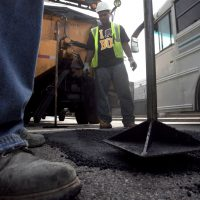 A proposed tax on incomes over $1 million will fund Massachusetts schools and infrastructure. Unless, of course, it won't.   Pictured: Boston Public Works workers Victor Duret, feet only at left, and Tyrone Odom, behind, both of Boston, fill a pothole with asphalt in Boston's Charlestown neighborhood. (Steven Senne/AP)