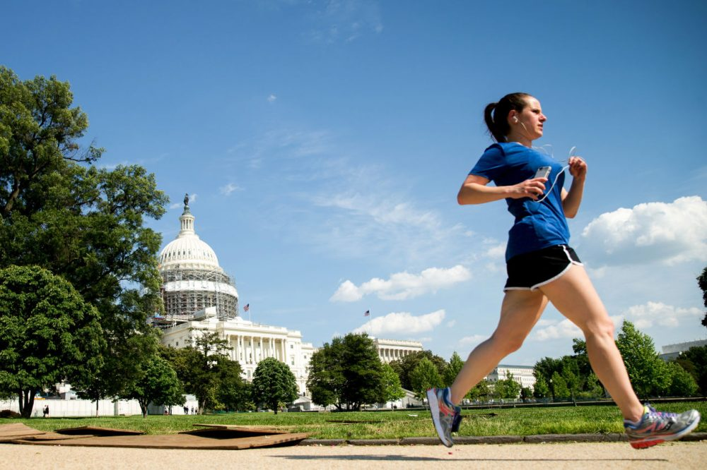 A woman jogs along the West Lawn on Capitol Hill in Washington, Tuesday, May 24, 2016, under blue skies after a recent rainy period. (AP Photo/Andrew Harnik)