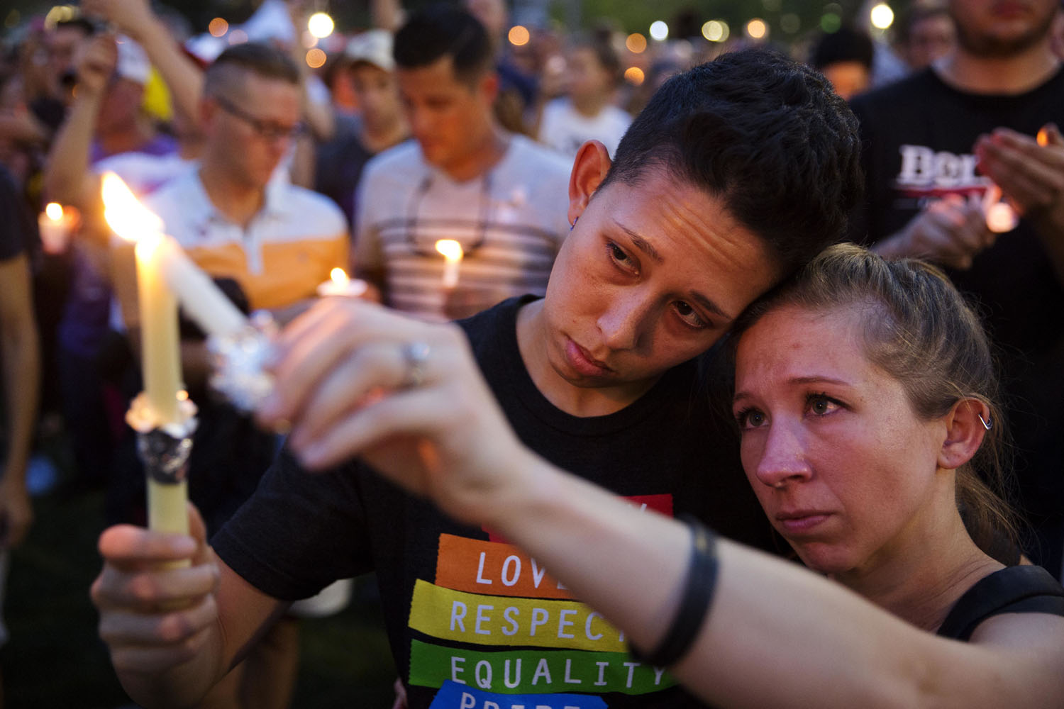 In this Monday, June 13, 2016 file photo, Jennifer, right, and Mary Ware light candles during a vigil in Orlando, Fla., for the victims of the mass shooting at the Pulse nightclub. (David Goldman / AP)