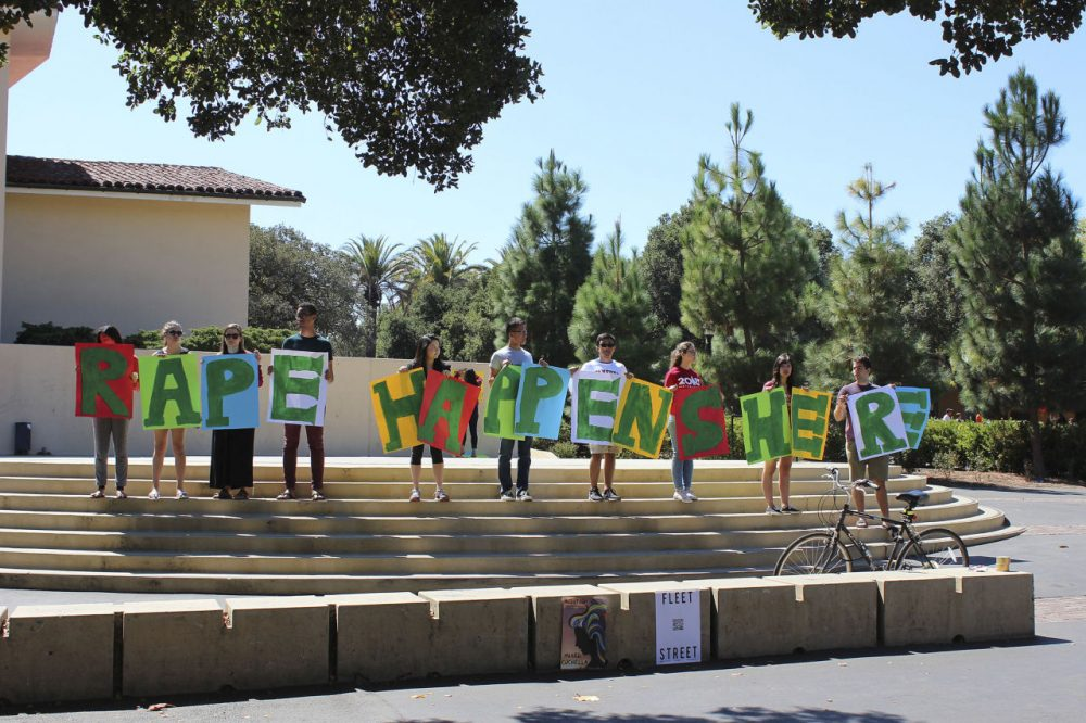 In this Sept. 16, 2015 photo provided by Tessa Ormenyi, students hold up a sign about rape at White Plaza during New Student Orientation on the Stanford University campus in Stanford, Calif.  (Tessa Ormenyi / AP)