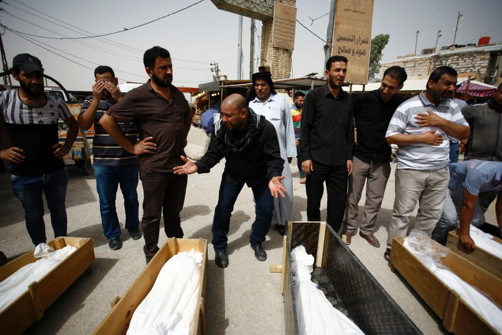 Iraqi men mourn over bodies after they lost five members of their family in a suicide bombing that ripped through Baghdad's busy shopping district of Karrada, during their funeral in the holy Iraqi city of Najaf on July 3, 2016.  The blast hit the Karrada district early in the day as the area was packed with shoppers ahead of this week's holiday marking the end of the Muslim fasting month of Ramadan, killing at least 75 people in the deadliest single attack this year in Iraq's capital. (HAIDAR HAMDANI/AFP/Getty Images)