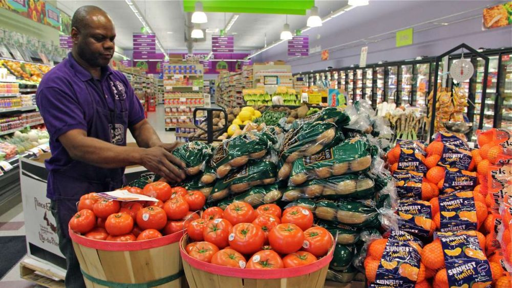 Produce manager Nate Sumpter arranges fresh fruits and vegetables at Fare & Square grocery in Chester. (Emma Lee/WHYY)
