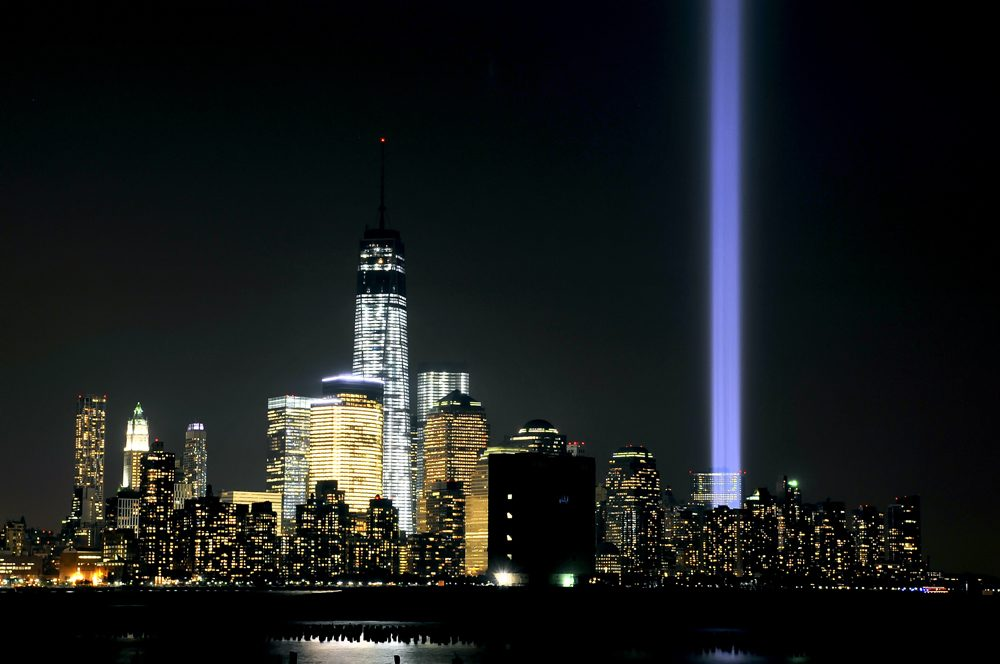 """The """"Tribute in Light"""" shines from the Manhattan skyline next to One World Trade Center to commemorate all those who were lost on 9/11 on September 11, 2013 in Hoboken, New Jersey. The lights are located at West and Morris streets in lower Manhattan. The nation is commemorating the anniversary of the 2001 attacks which resulted in the deaths of nearly 3,000 people after two hijacked planes crashed into the World Trade Center, one into the Pentagon in Arlington, Virginia and one crash landed in Shanksville, Pennsylvania. (Michael Bocchieri/Getty Images)"""