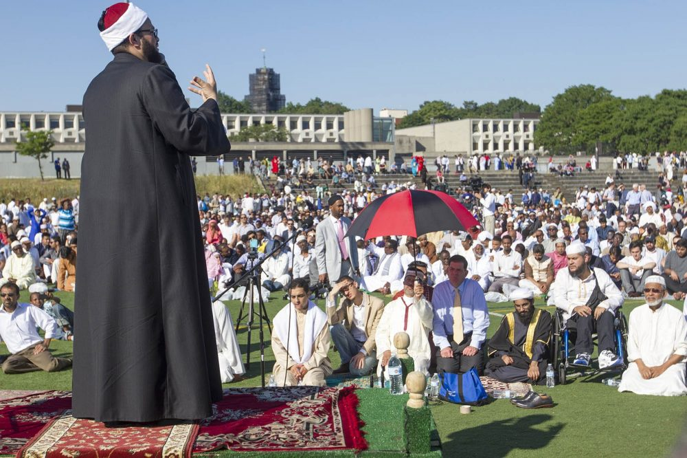 Imam Yasir Fahmy speaks at an Eid prayer service at Madison Field, across from the Islamic Society of Boston Cultural Center, on Wednesday morning. Mayor Marty Walsh (underneath the umbrella) listens. (Joe Difazio for WBUR)