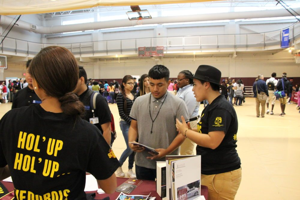 Huston-Tillotson graduate Angelica Erazo, 22, gave her pitch about the benefits of historically black colleges and universities to Luis Betancourt, 15, a high school freshman already thinking about college. The Houston Independent School District held an HBCU college summit at Texas Southern University in May. (Laura Isensee/Houston Public Media)