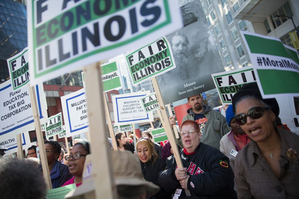 Demonstrators, protesting the state of Illinois budget stalemate, rally in the Loop before marching to the Chicago Board of Trade Building where they bolcked all of the entrances to the building on November 2, 2015 in Chicago, Illinois. (Scott Olson/Getty Images)