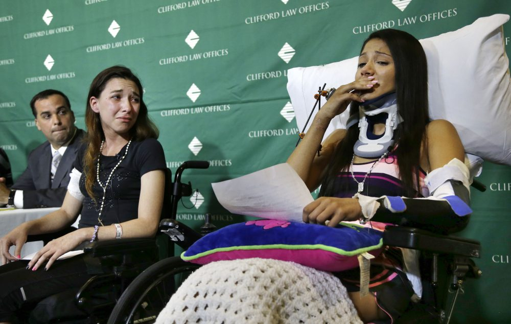 Circus acrobats Julissa Segrera, second from left, of the United States, and Dayana Costa, right, of Brazil, are tearful as Costa reads a statement to members of the media at Spaulding Rehabilitation Hospital on May 17, 2014. (Steven Senne/AP)