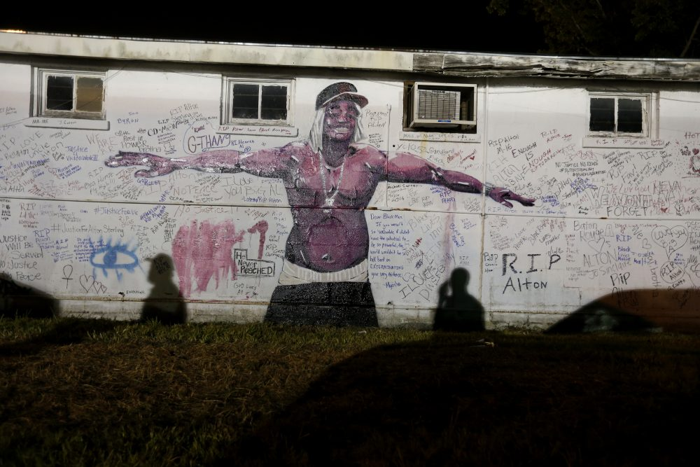 Shadows fall on a newly painted mural of Alton Sterling next to the Triple S convenience store in Baton Rouge, La., Wednesday, July 6, 2016. (Gerald Herbert/AP)