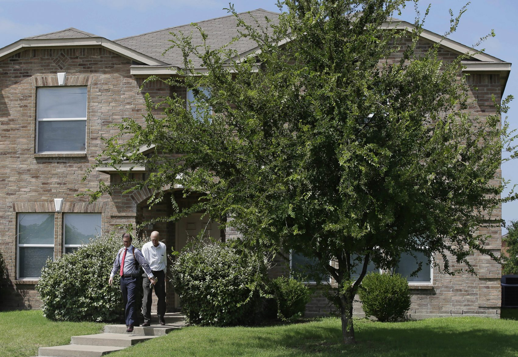 Investigators leave the home of Micah Xavier Johnson in the Dallas suburb of Mesquite, Texas, Friday, July 8, 2016. (LM Otero/AP)